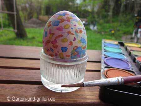 Osterei bemalt mit Wasserfarben und Pinsel.